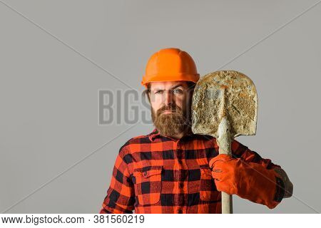 Construction Worker Holds Shovel. Repairment. Workman With Spade. Builder In Work Gloves Hold Spade.