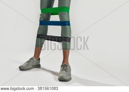 For Stronger Legs. Close Up Of Legs Of Sportive Woman Doing Leg Exercises Using Fitness Gum, Three E
