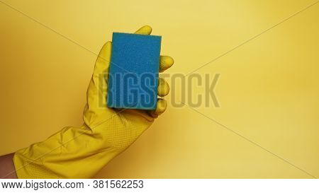 Sponge For Washing Dishes In Hand. Hand In A Latex Glove Isolated. A Hand In A Glove Holds A Sponge