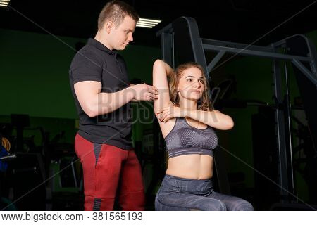 The Trainer Helps The Girl Perform The Dumbbell Exercise.