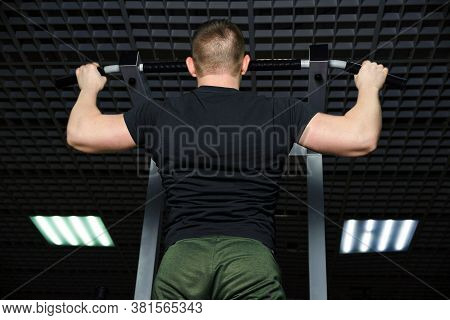 The Guy Performs A Pull-up Exercise On The Simulator.