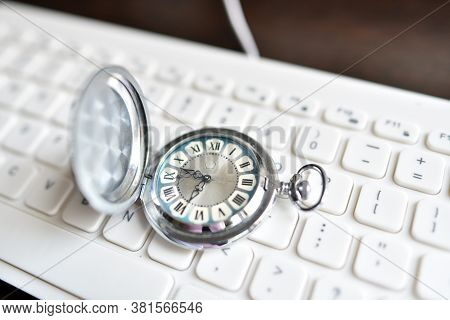 Antique Vintage Pocket Watch Lies On White Keyboard. The Concept Of Modernity, Manufacturability, Ar