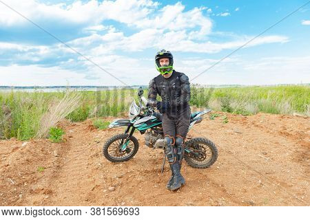 A Man In Motorcycle Equipment Sits On An Enduro Motorcycle.