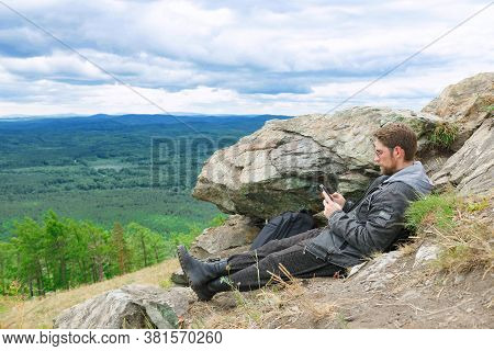 The Guy Is Sitting On The Top Of The Mountain With A Phone In His Hands.
