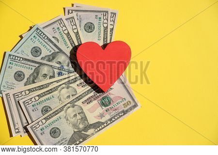 Top View Of Red Heart On American Dollars, Yellow Background.red Heart On A Pile Of Banknotes Using