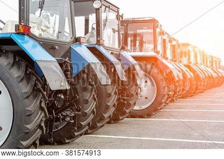 Many Different Tractors Standing In Row At Agricultural Fair For Sale Outdoors.equipment For Agricul