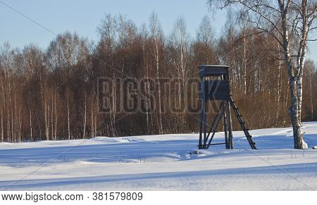 A Tower For Hunting Wild Animals On The Edge Of A Snow-covered Field In Winter. Hunting Tower On The