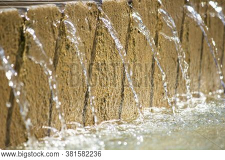 Extreme Close Up Of The Bottom Tier Of A Water Fountain With Water Pouring Through Repetitive Groove