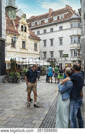 Graz, Austria. August 2020. A Sweet Maiden And Hearty Lad Clad In Traditional Costume Pirouette Thre