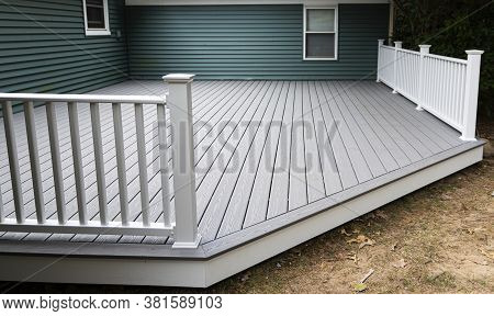 New Composite Deck On The Back Of A House With Green Vinyl Siding.with Whie Railings.