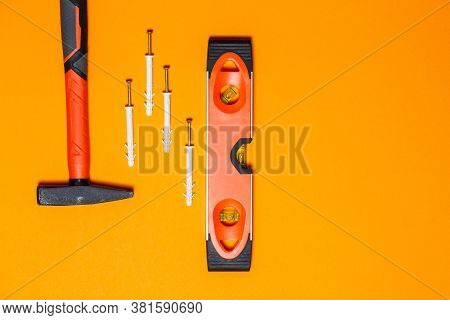 Tools For Repair. Hammer For Nails, Level, Dowel In The Wall On An Orange Background. Toolkit For Th