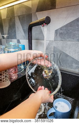 Hands With A Sponge Wash The Pan Cover Under Water, The Housewife Mistress Washes A Blue Mug In The