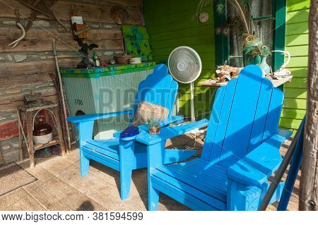 Carthage Usa - September 7 2015; Colorful Cluttered Rustic Farmhouse Porch With Bright Blue Chairs