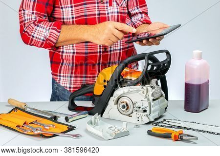 Workman Calculating The Price At Repair Of Chainsaw. Repair Of Chainsaws,gasoline Powered Tools. Rep