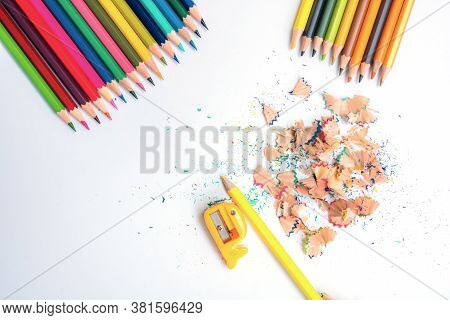 Top-down Of The Colored Pencils And Pencil Shavings Along With Yellow Pencil Frog On A White Backgro