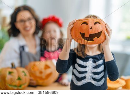 Happy family preparing for Halloween. Mother and children in carnival costumes carving pumpkins at home.