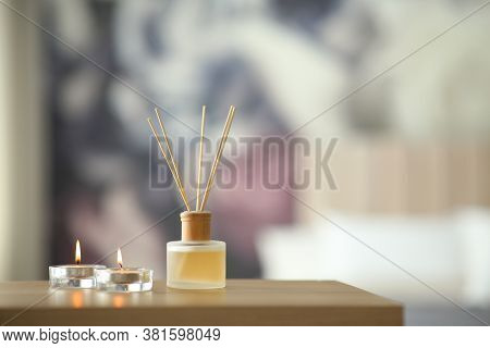 Aromatic Reed Air Freshener And Scented Candles On Table Indoors. Space For Text