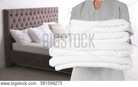 Chambermaid With Clean Folded Towels Near Bed In Hotel Room, Closeup