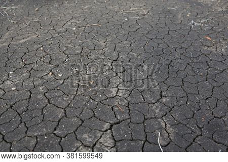 Crack Earth And Dry Black Soil. Drought On The Ground