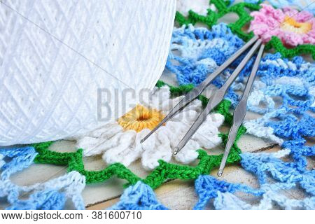 A Close Up Image Of Three Metal Crochet Hooks On A Blue And White Crochet Doily.