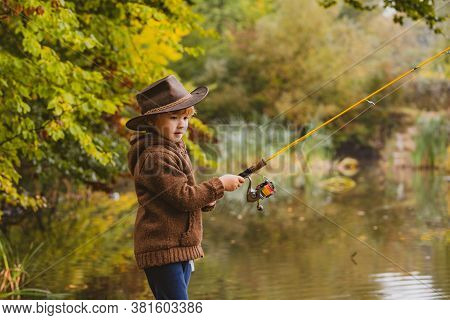 Kid With Fishing Rod. Child Learning How To Fish, Holding A Rod On A Lake