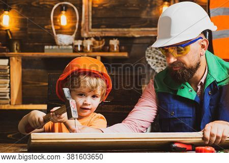 Cute Little Son And Father In Hard Hat Holding Wooden Plank And Hammer. Boy Helping His Dad At Home
