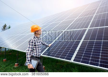 Male Engineer In A Helmet With A Tablet In His Hands Standing Near The Solar Panels, Looking Up. Gre