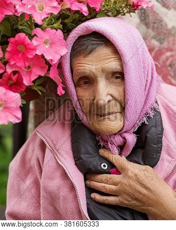 Photo Of An Elderly Senior 85-year-old Woman Adjusts A Pink Kerchief On Head Among Petunias And Smil