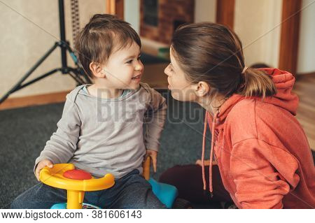 Caucasian Mother Speaking With Her Son Playing With A Car Toy In The Living Room Face To Face