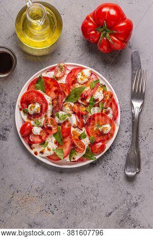 Italian Caprese Salad With Sliced Tomatoes, Mozzarella Cheese, Basil, Olive Oil, Balsamic Vinegar.