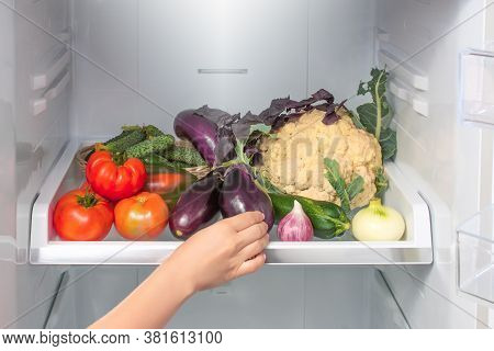 Woman Takes The Eggplant From The Open Refrigerator. Woman's Hand Reaches For The Vegetables On The