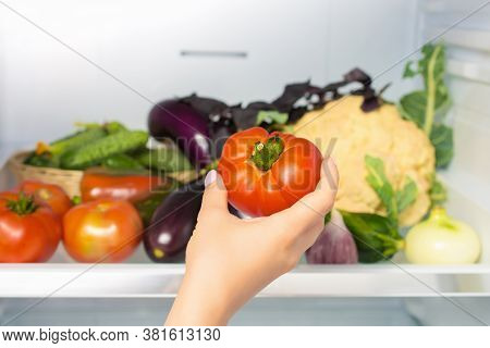 Woman's Hand Picks Up Tomato From The Refrigerator Shelf. Hand Takes A Tomato From The Refrigerator.