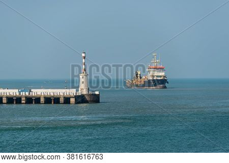 Mormugao, Goa, India - November 23, 2019: View On The Mormugao Breakwater Lighthouse And Ship At Sea