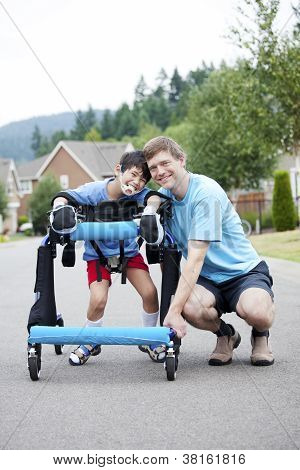 Father Kneeling Next To Disabled Son Standing In Walker