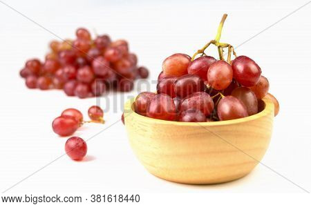 Red Grapes In Wooden Cup On White Background