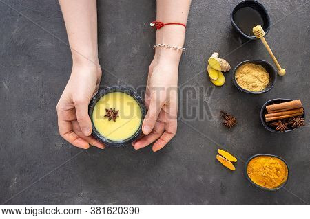 Woman Holding Cup With Golden Milk On Concrete Background. Famous Ayurvedic Beverage With Ingredient