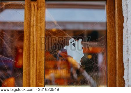 Halloween Street Decor. Paper Cut Ghost And Cobweb On Door Or Window At Store, Festive Decoration Of