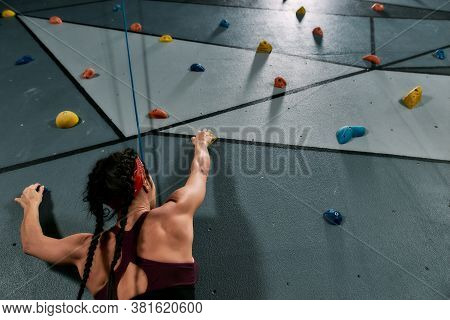Woman In Safety Equipment And Harness Reaching Boulder, While Training On The Artificial Climbing Wa