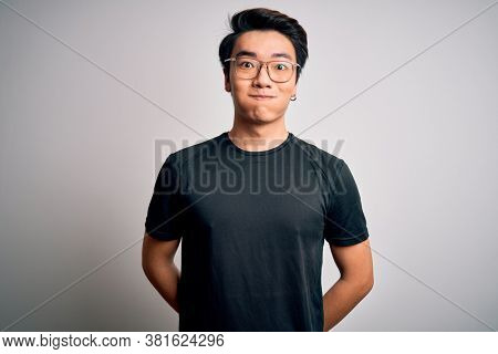 Young handsome chinese man wearing black t-shirt and glasses over white background puffing cheeks with funny face. Mouth inflated with air, crazy expression.