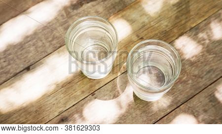 Two Glass Of Water On A Wooden Table.