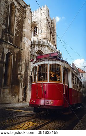 Traditional Old Red Tramcar Cable Electric Trolley Running Over The Streets Of Alfama Historical Dis