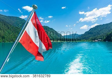 Austria Flag During A Boat Ride On A Lake In The Alps On A Beautiful Summer Day.