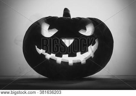 Happy Halloween. Creepy Pumpkin Jack-o-lantern In Smoke. Black And White Image, Backlight.