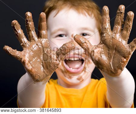 Very Much Smeared In Chocolate Hands Of The Child, Close-up Traces Of Melted Milk Chocolate On The S
