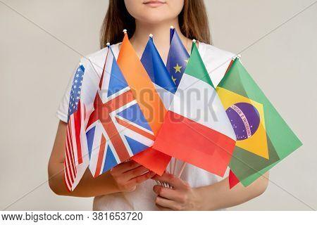 World Community. Global Organization. Woman Holding International Flags Isolated On Blur Light Backg
