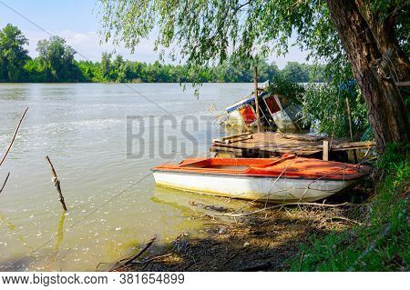 Wrecked Small Fishing Boat Is Partially Flooded, Standing On The Coast Of Wide River.