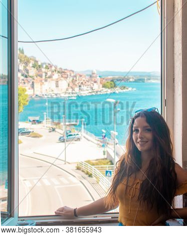 Attractive Brunette Posing And Smiling Near A Window, Coastal Town Of Sibenik, Croatia In The Distan