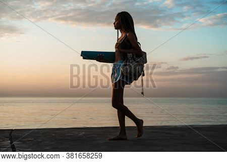 Image of calm african american girl in sportswear walking with mat on concrete promenade outdoors