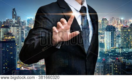 Double Exposure Of Business Man Pointing Space On City Night Background, Advertisement Concept