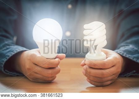 Hands Holding Spiral Bulb And Led Light Bulb, Saving Energy Efficiency And And Accounting Finance Co